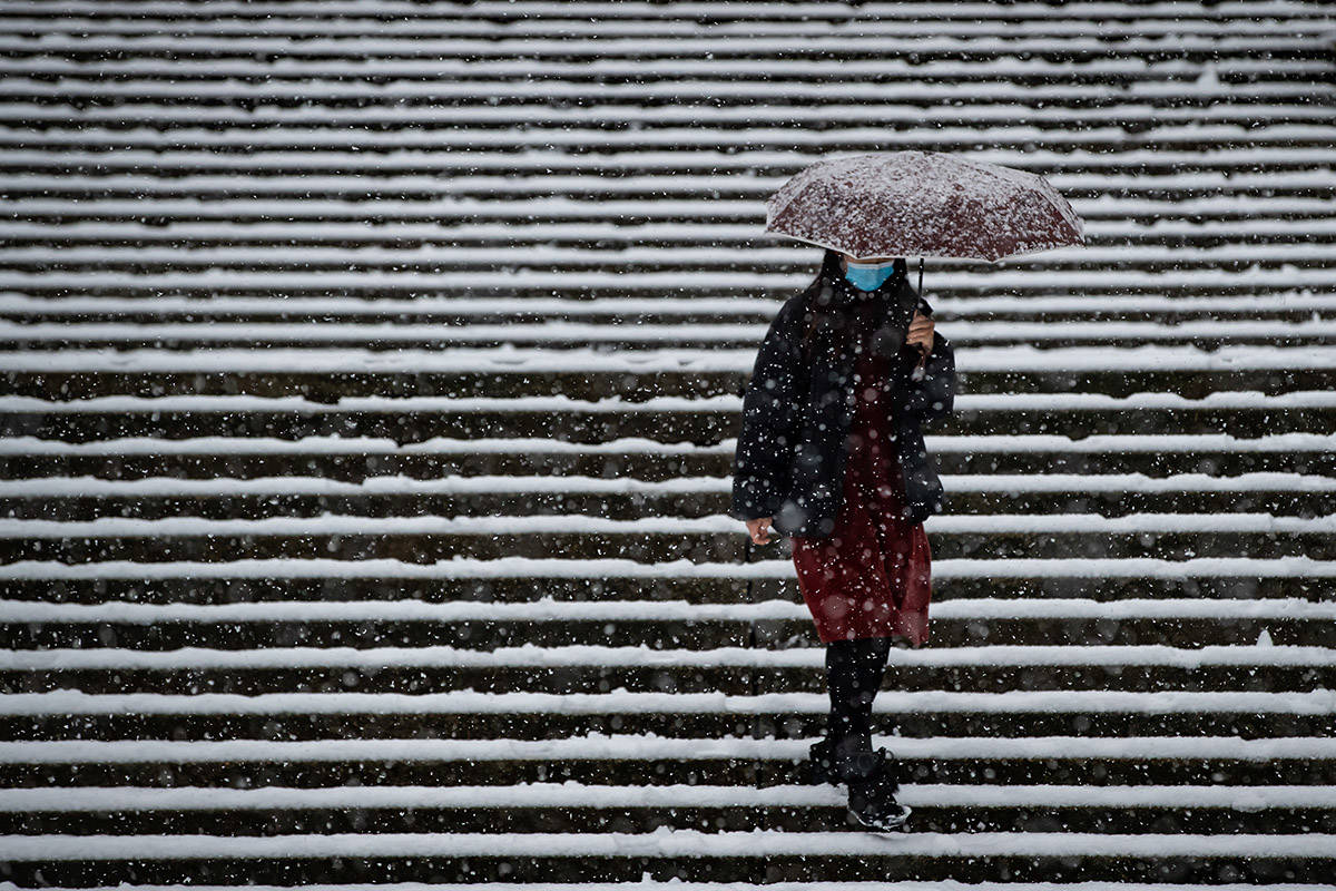 A woman wearing a face mask to curb the spread of COVID-19 carries an umbrella while walking down steps on the Simon Fraser University campus, as heavy snow falls in Burnaby, B.C., on Monday, December 21, 2020. THE CANADIAN PRESS/Darryl Dyck